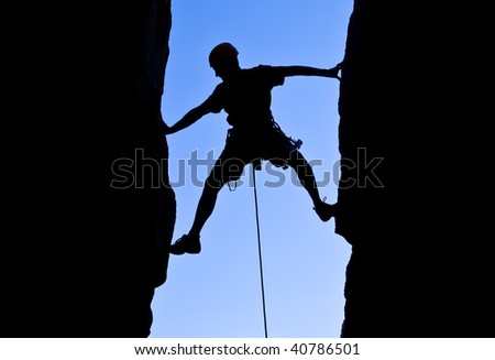 Rock climber silhouetted as he climbs up a chimney in Joshua Tree National Park, California.