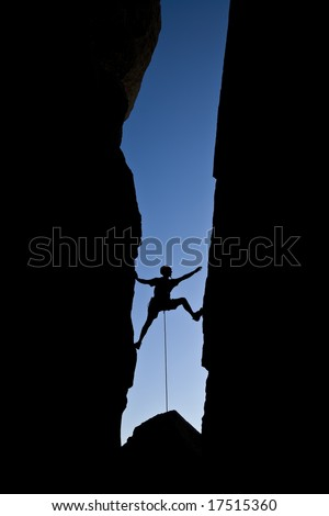 Rock climber silhouetted as he climbs up a chimney in Joshua Tree National Park, California, on a summer day.