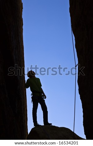 Rock climber silhouetted as he contemplates his route up a chimney in Joshua Tree National Park.