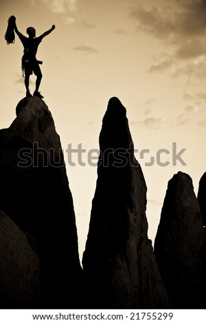 Rock climber silhouetted on the summit of a rock spire in Joshua Tree National Park, California, on a summer day.