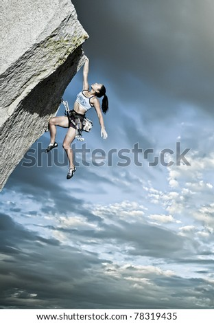 Rock climber struggles for her next grip on a challenging ascent.