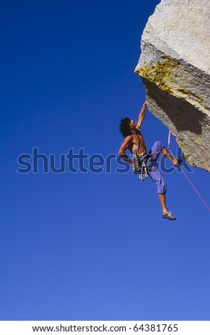 Rock climber struggles for his next grip on a overhanging cliff.