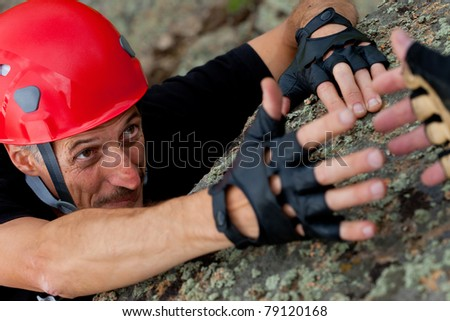 rock climber take hand of friend - stock photo