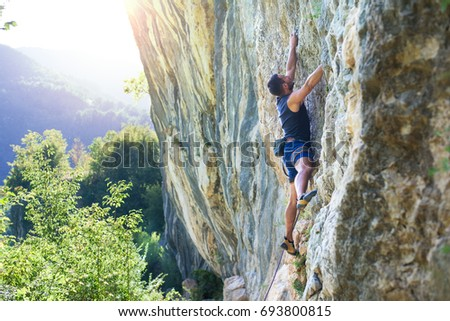 Rock climber with hand in chalk bag hanging on boulder #693800815