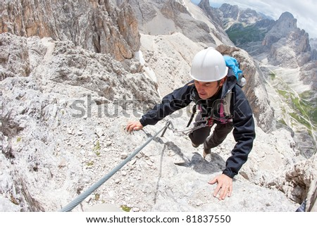 Rock climber with helmet. Dolomites, Italy.