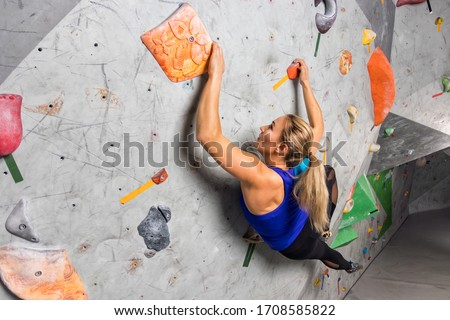 Rock climber woman hanging on a bouldering climbing wall, inside on colored hooks Stock photo ©