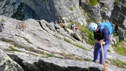 rock climbers traverse and climb the Clocher de Planpraz climbing route in the French Alps above Chamonix