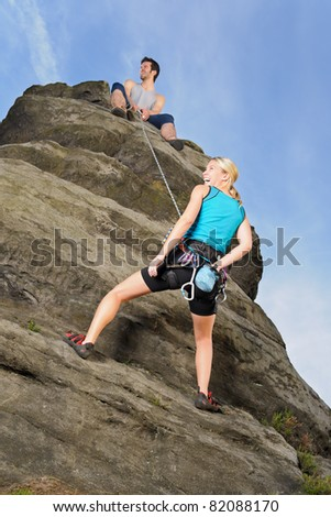 Rock climbing active young woman  man holding rope on top