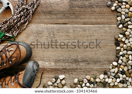 Rock climbing background with safety rope and traditional mountain hiking shoes on old wood board plank with alpine river pebbles