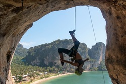 Rock climbing in Thailand. Climber (girl) in helmet hangs upside down on the rope on the ceiling of the cave. Tonsai beach, Krabi Province.