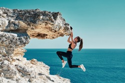 Rock climbing. Sport. Active lifestyle. Athlete woman hangs on sharp cliff. Seascape. Outdoors workout. High resilience
