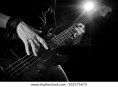 rock concert: bass guitarist playing on stage
