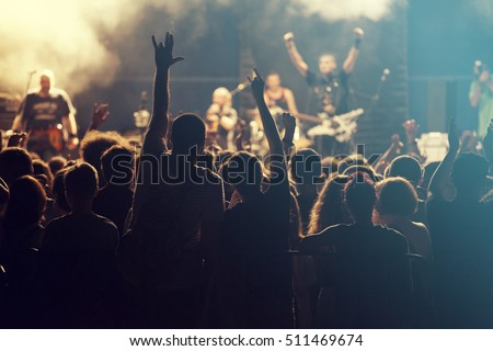 Rock concert, cheering crowd in front of bright colorful stage lights