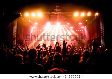 Shutterstock Rock concert, silhouettes of happy people raising up hands
