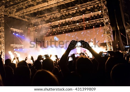 Rock concert, silhouettes of happy people raising up hands in front of bright stage lights