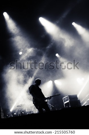Rock concert stage. Guitarist playing on electric guitar.