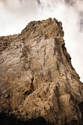 Rock face in Cabo San Lucas, Mexico. View looking upward from a boat in the water below.