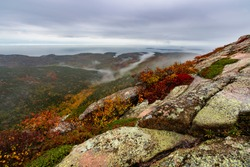 Rock face sloping down into valley on top of mountain overlooking atlantic ocean in acadia national park maine on a foggy fall morning at sunrise