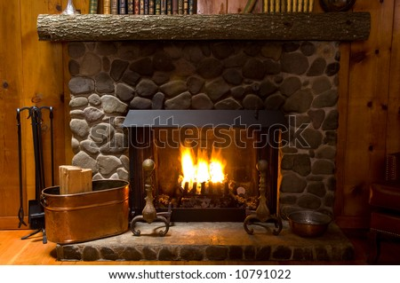 rock fireplace in a mountain cabin with fire cropped to just show fireplace natural lighting