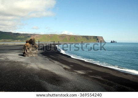 Rock formation on black volcanic beach at Cape Dyrholaey, South Iceland, with mount Reynisfjall on the background #369554240