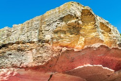 rock formations in yellow and pink on the sky background. rare karst shapes.White chalk and red sandstone geological layer.rock structure close-up. view of the geologic history