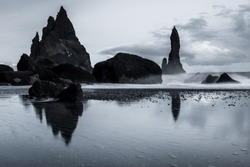 Rock formations on a black sand beach in Iceland with reflection in the Sea and a dark sky in misty moody weather with dark colors and a rough sea