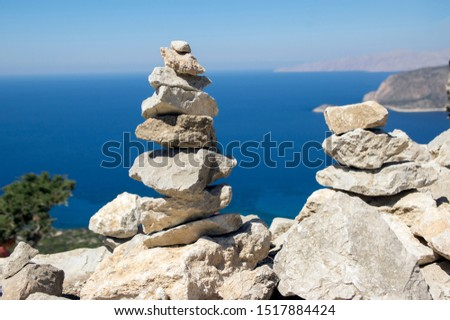 Rock group of stones cairn in daylight, poise light pebbles on rock with blue natural ocean natural background, zen like sculpture, simplicity, harmony and balance