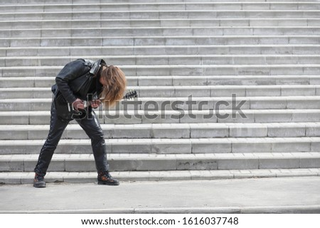 Rock guitarist on the steps. A musician with a bass guitar in a leather suit. Metalist with a guitar on the background of industrial step.
