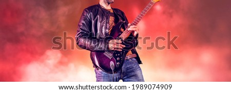Rock guitarist plays solo on an electric guitar. Artist and musician performs like rockstar. Guitar player performs on stage.  Foto stock ©