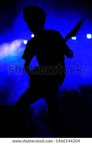 Rock guitarist silhouette with blue background at a concert, India
