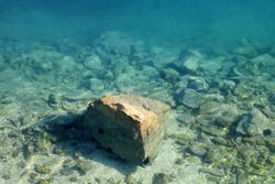 Rock in the shallow sea. Selective focus.