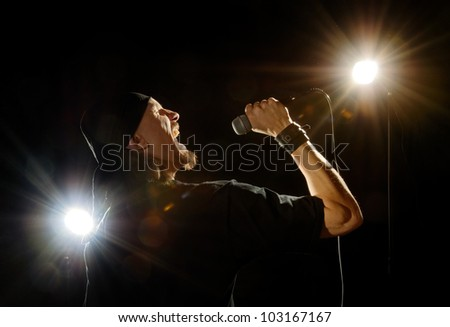 rock metal singer with mike on stage lightened