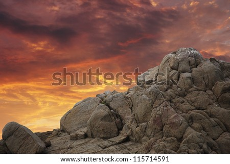 Rock mountain cliff over sunset sky background