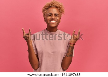 Rock music and rock n roll. Portrait of a contented punk lady in casual clothes who closes her eyes with pleasure and makes horns with her fingers. Woman shows a rock sign on a pink wall background. Foto stock ©
