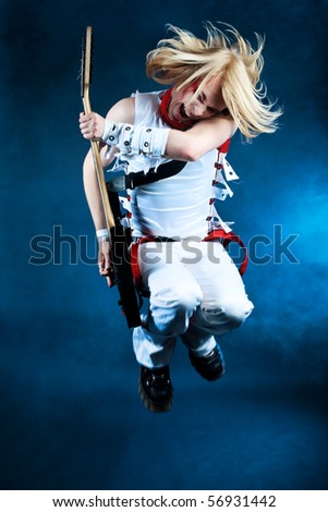 Rock musician is playing electrical guitar. Shot in a studio.