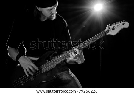 rock musician, playing on bass guitar, black and white