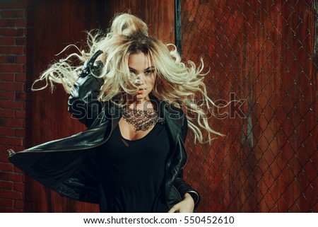 Stock Photo Rock'n'roll girl, young beautiful woman dances in dark alley, against the mesh fence