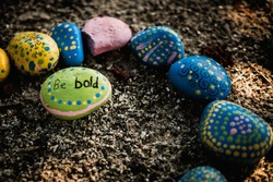 rock painted green with polka dots and be bold written on top in surrounded by painted rocks
