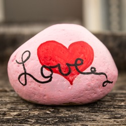 Rock painted pink with a heart and the works love sitting on a grainy piece of wood and intentionally blurry background.  Bokeh.  Close up and background