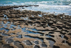 Rock pool by the beach coastal tourist destination seaside resort blue vibrant water reflections by the shore