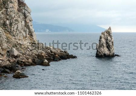 """Rock """"Sail"""" near of the Yalta city. Crimea. Overcast weather over the sea. Rain over the sea. Travel photo #1101462326"""