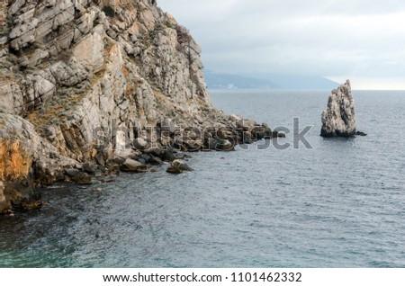 """Rock """"Sail"""" near of the Yalta city. Crimea. Overcast weather over the sea. Rain over the sea. Travel photo #1101462332"""