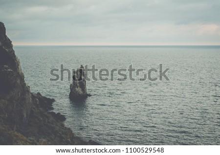 "Rock ""Sail"" near the city of Yalta. Crimea. Overcast weather over the sea. #1100529548"