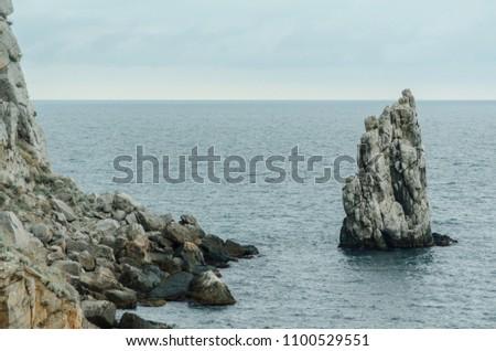 "Rock ""Sail"" near the city of Yalta. Crimea. Overcast weather over the sea. #1100529551"