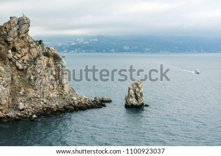 "Rock ""Sail"" near the city of Yalta. Crimea.  The ship sails to the sea. Overcast weather over the sea. #1100923037"