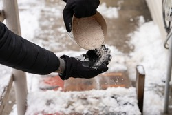 rock salt ice melt is being spread on your walkway to melt the ice and snow from your path