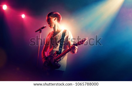 Rock singer with a guitar in stage lights #1065788000