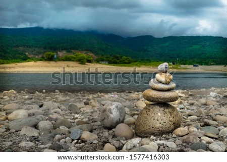 Rock stack on the stones symbolizing harmony, balance, and tranquility. Clouds and mountain in the background at Bholagonj, Sylhet.