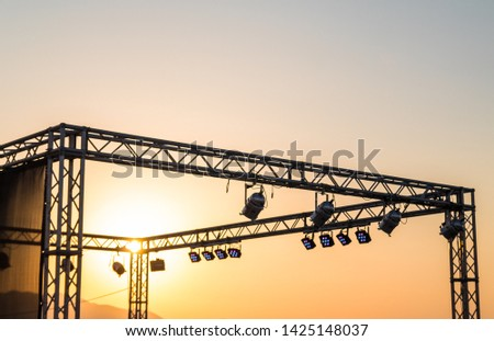 rock stage iron beams and stage lights against the setting sun. sunset. concert. heat. summer #1425148037
