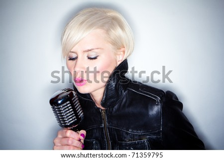 Rock star.Sexy Girl singing in retro mic on grey background ringflash - stock photo